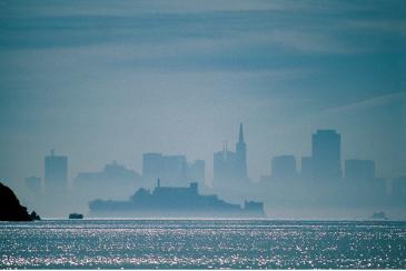 Trügerisches Idyll im legendären Nebel: Die Gefängnisinsel Alcatraz vor der Silhouette der Skyline von San Francisco. (c) Phil Coblentz, San Francisco CVB